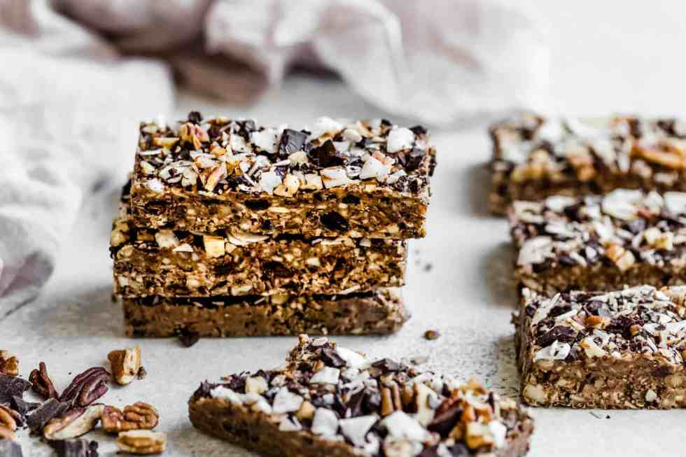 three protein bars stacked with coconut flakes, pecans and chocolate chips