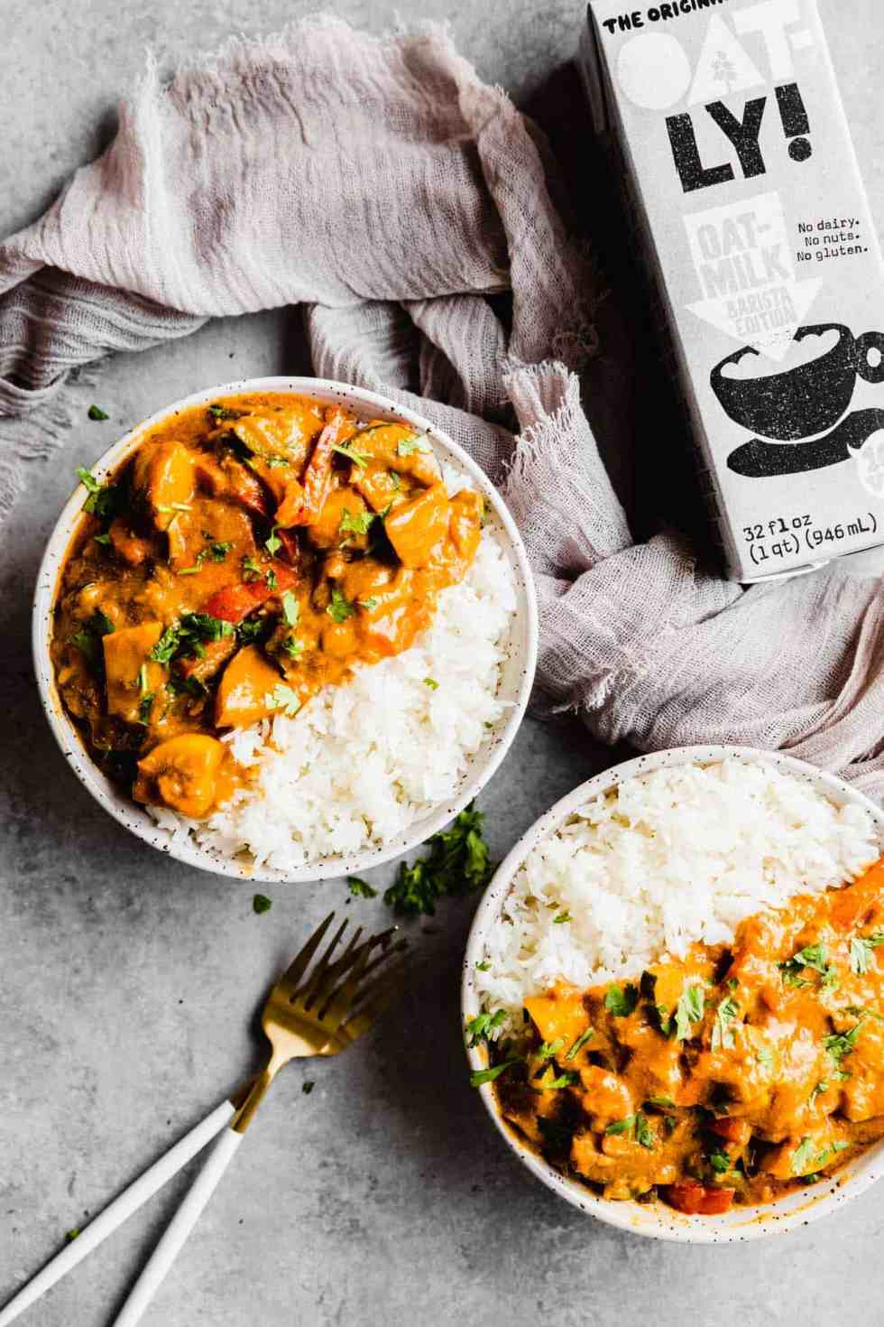 two bowls of Thai red curry with white rice and a container of Oatly
