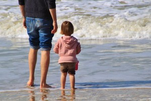 A kid standing on the beach with a parent