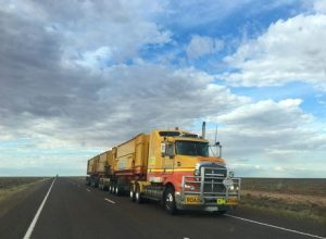 A big yellow truck on an open road