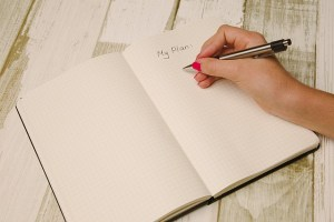 a person writing a plan in a notebook in order to cut moving costs