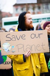 """A young man holds a piece of cardboard where """"Save our planet"""" is written"""