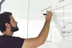 Man with a marker in his hand is writing on the board.