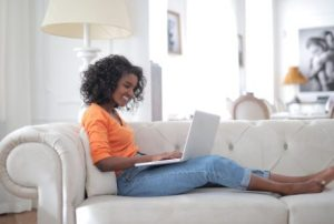 There is a smiling woman sitting on a sofa, typing something on her laptop.