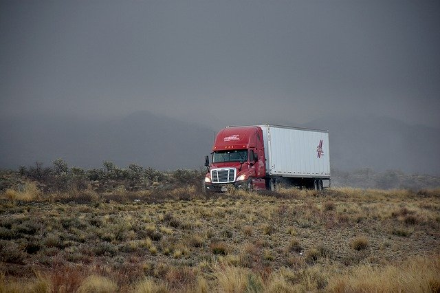 A moving truck going down the road on a cold and stormy weather, one of the ways to move to another state with limited resources.