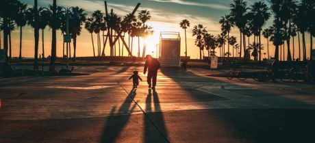 A father and his son walking during the sunset.