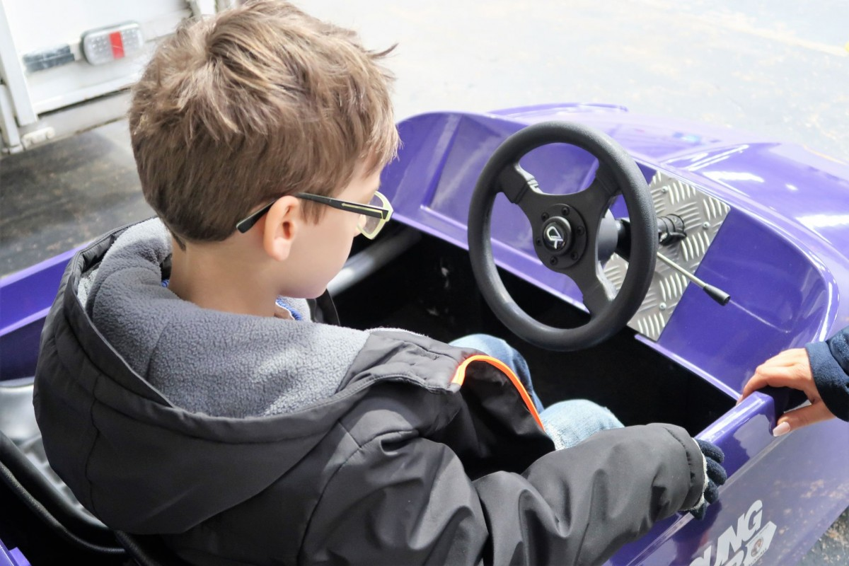 Small boy child sits in the drivers seat of the Purple Firefly, purpose built small car. He is being shown how to work the controls, (person is off camera)