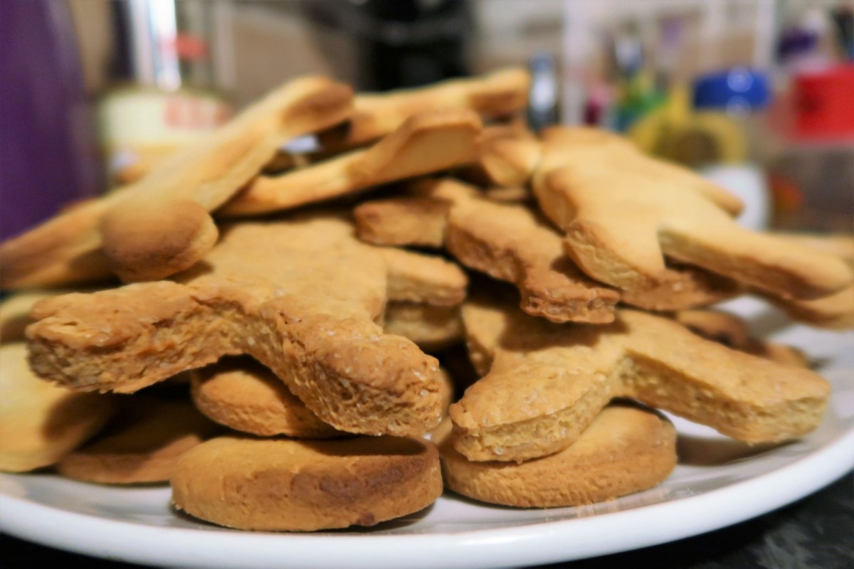 a plate full of freshly baked gingerbread men and biscuits.