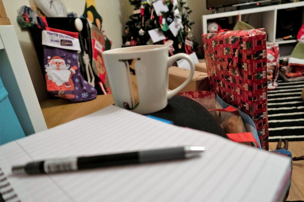Notebook with a pen resting ontop. a cup of tea in the background with presents, stockings and a christmas tree behind the cup of tea.