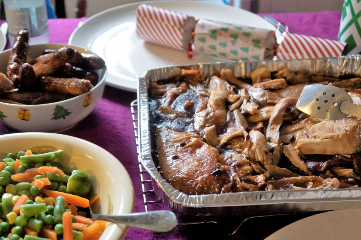 A bowl of mixed vegetables at the bottom left of the photo, top left is a bowl of chipolata sausages. The top is a large plate with a single christmas cracker across. Below to the right is a medium sized tin foil tray with sliced turkey and gravy.