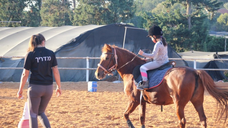 An 8-year-old learns how to ride therapeutic horse Tika. (Courtesy of INTRA)