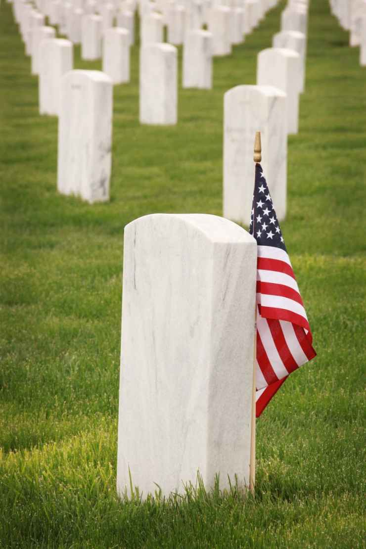 flag of u s a standing near a tombstone