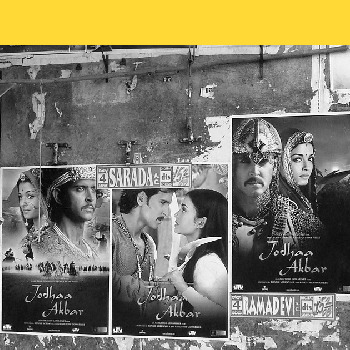 Black and white posters of Bollywood movies cover a wall, yellow stripe above