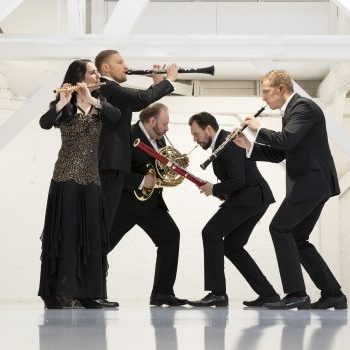 Carion Woodwind Quintet members pose dramatically in a white loft