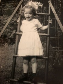 Rebecca Kaiser Gibson stands on ladder of play set in black and white childhood photo