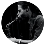 Black and white image of black man with dreadlocks playing saxophone