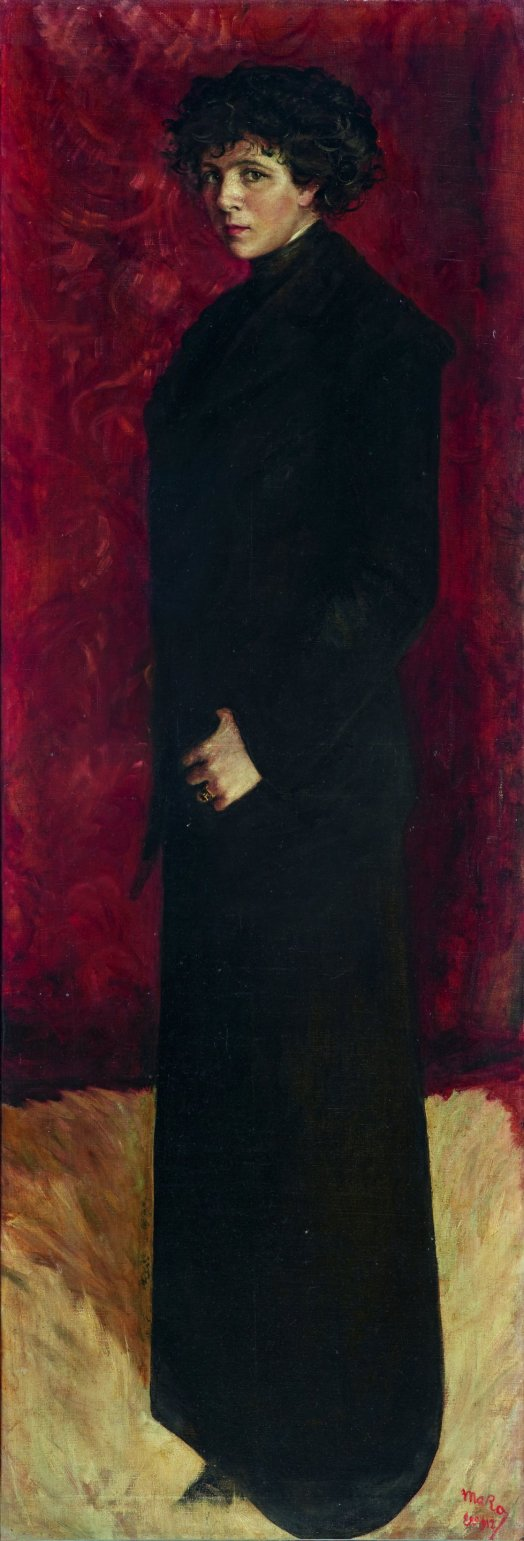 Marisa Roësset dressed in black against a red curtain
