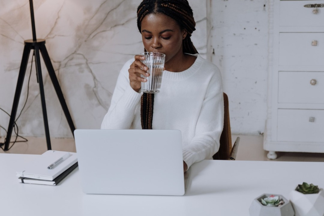 black girl sitting at computer drinking water