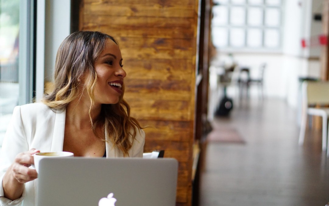 Latina woman on laptop smiling