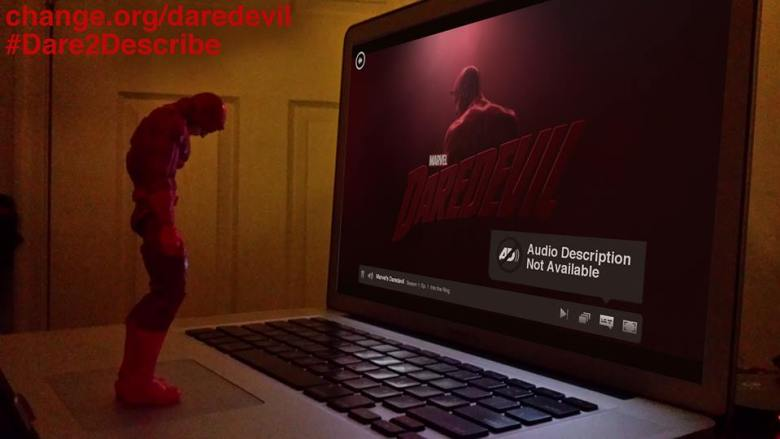 """A Daredevil action figure stands on a laptop keyboard, his head and shoulders slumped down dejectedly. On the screen is the opening sequence from the Netflix series Marvel's Daredevil with an alert window that reads: """"Audio Description Not Available."""""""
