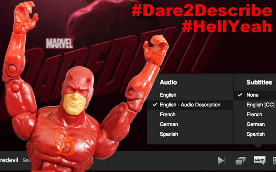 """A smiling Daredevil action figure sits in front of a computer monitor, arms raised above his head triumphantly. The opening sequence from the Netflix series Marvel's Daredevil plays on the screen behind him with a newly added audio track selected in the settings menu that reads: """"ENGLISH - AUDIO DESCRIPTION."""" In the corner are two hashtags in red text: #Dare2Describe #HellYeah"""