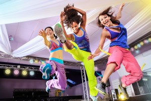 young women in sport dress jumping at an aerobic and zumba exerc