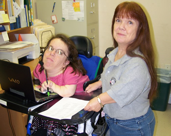Photo of Bobbie Singletary at work, helping someone on the computer.