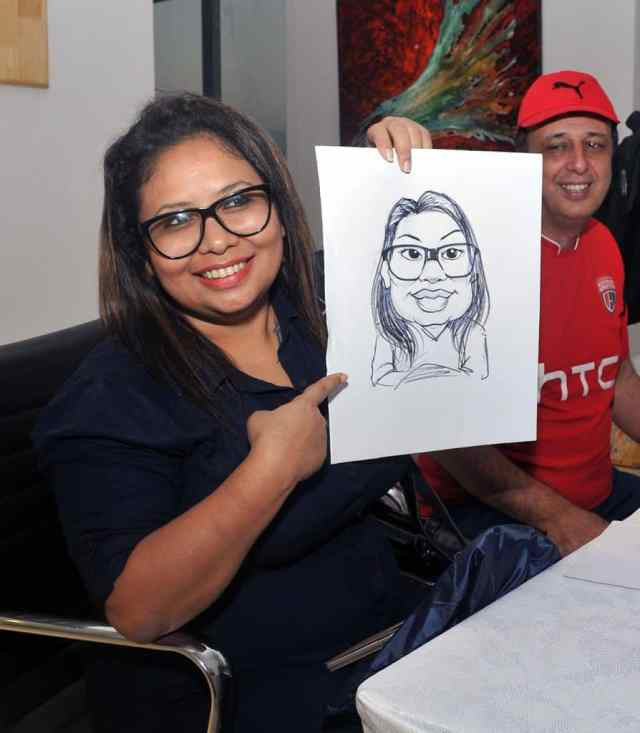 RJ Mandy showing her caricature drawn by Pritom Boro at the event