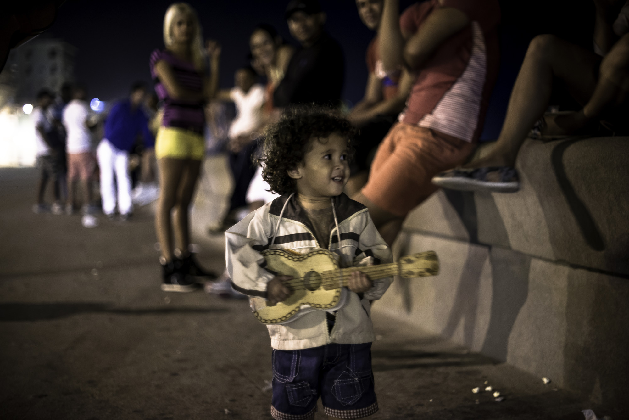 A small boy plays along to his parents' boombox on the Malecón.