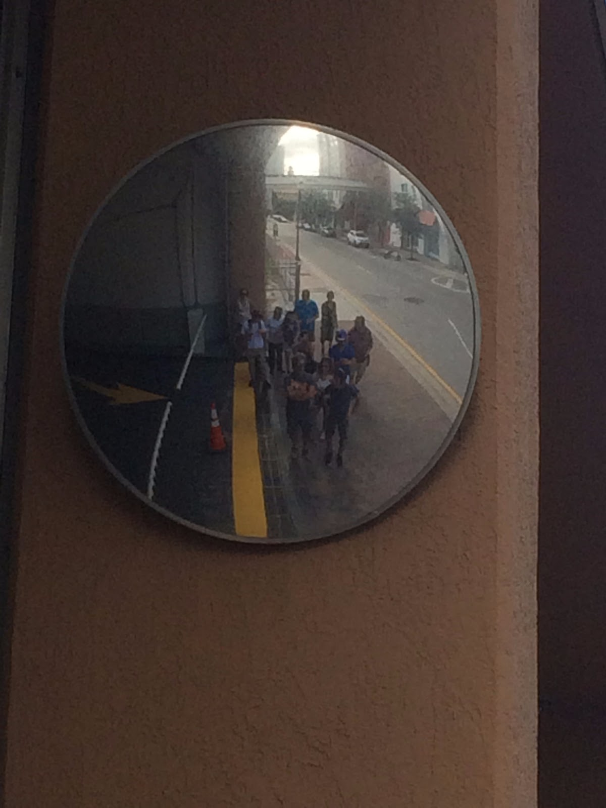 Heather directs the group to gather at a mirror and take a picture together.