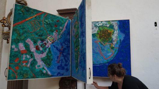 Lucinda Linderman painting the edges of her installation, a series of maps tracking the impact of nature on the villa.