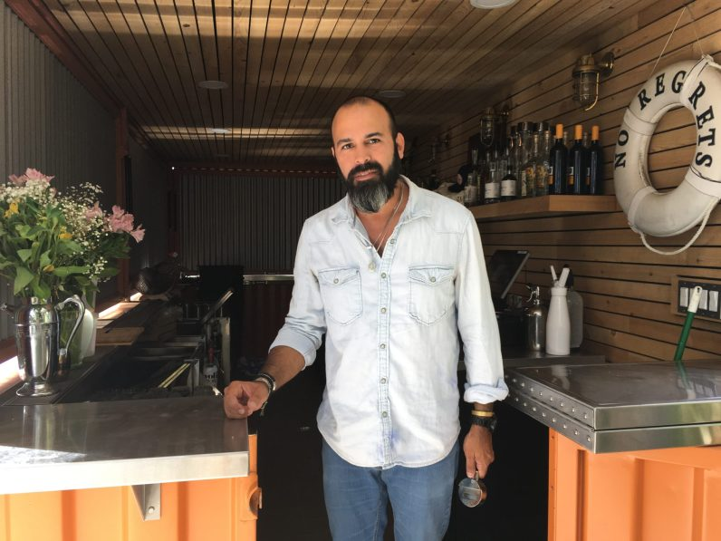 Casa Florida co-founder Gaston Gonzalez inside of a shipping container they converted into a bar. They are hosting pop-ups until they can open their doors. (Credit: Roshan Nebhrajani/The New Tropic)