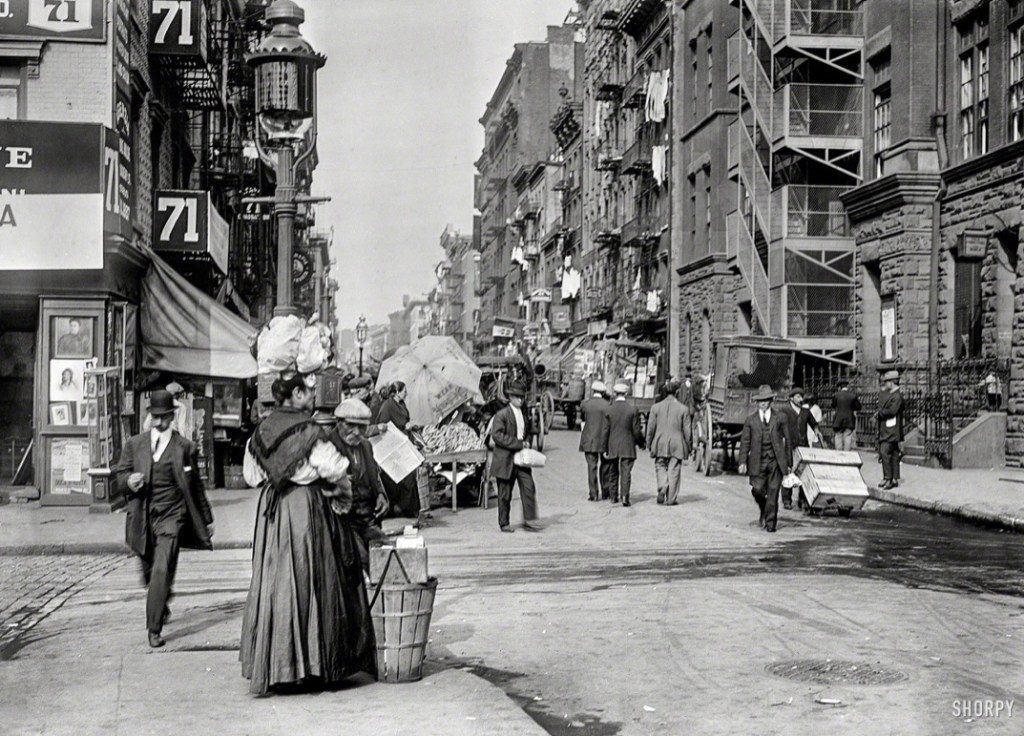 A 1920s street scene featuring street traffic and the typical fashion of the day. Notice how it was so common for people to walk in the center of the street. So few owned automobiles that it didn't even matter.