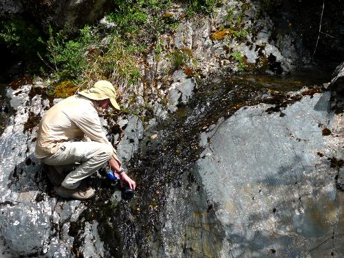 Filling a water bottle from a stream