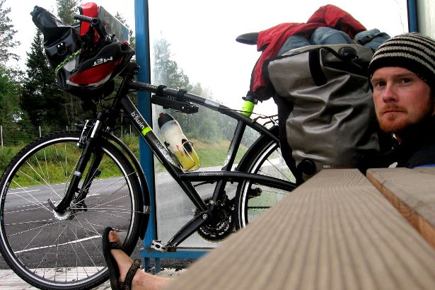 Cyclist seeking refuge in a bus shelter