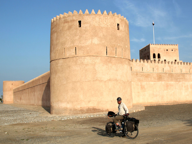 Cycling past an Omani desert fort