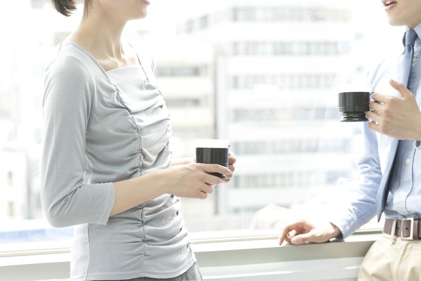 オフィスでコーヒーを飲みながら会話する男女