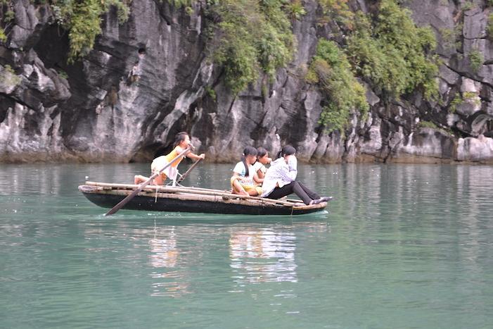 Niños remando en la Bahía de Halong