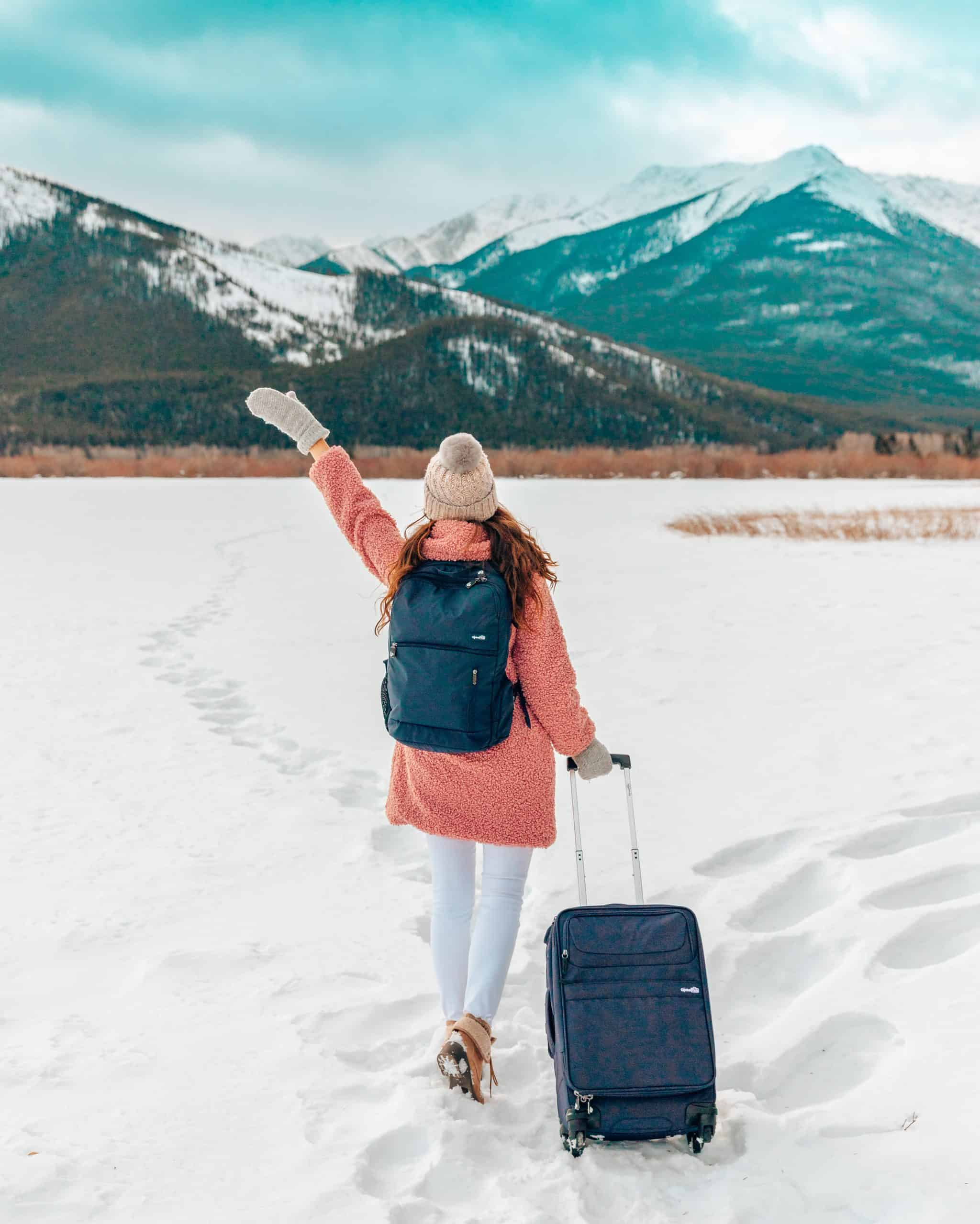Girl standing on frozen lake with backpack and suitcase - The Next Trip