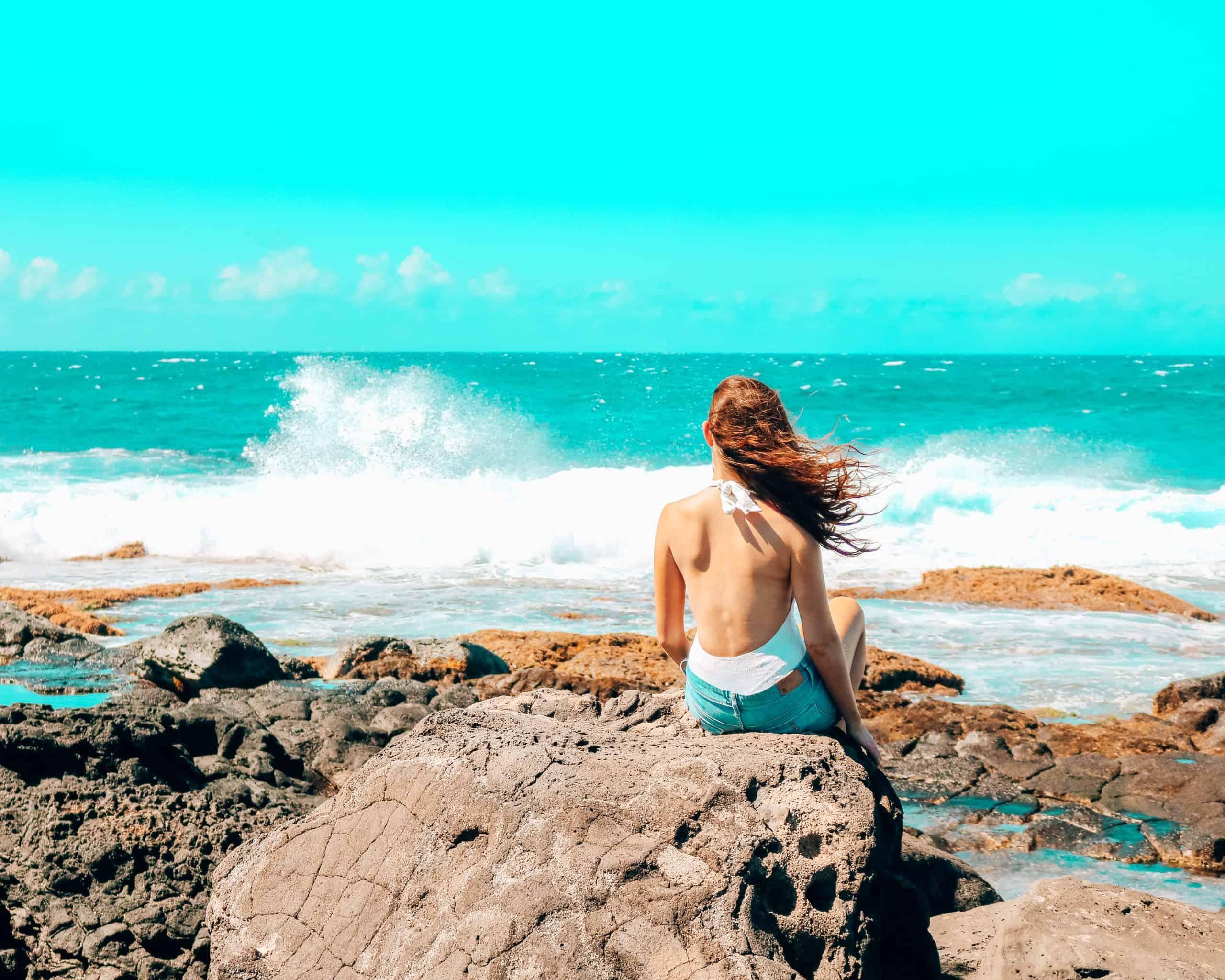 Bettina looking at a crashing wave in Hawaii