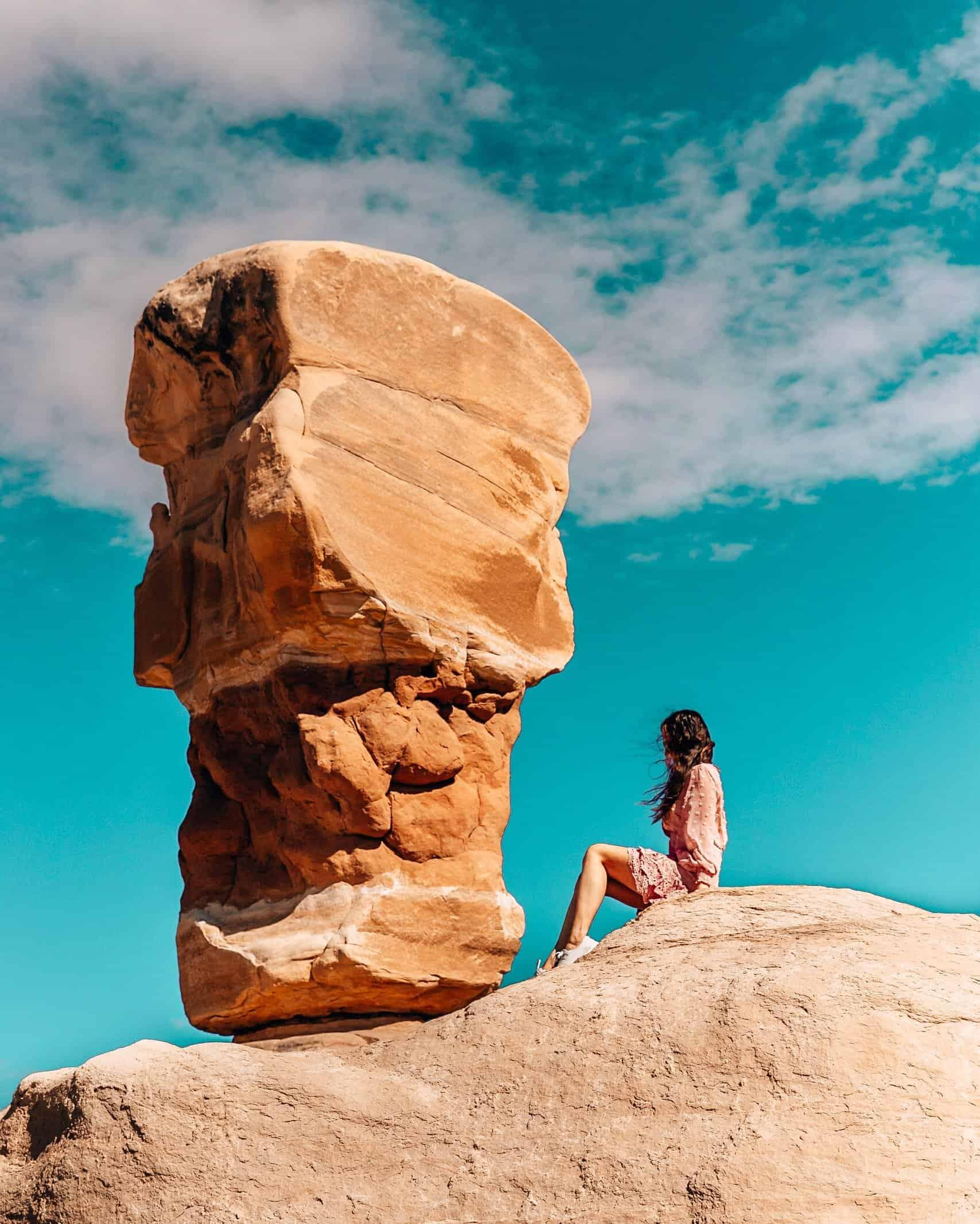 Girl Sitting in front of Hoodoo at Devil's Gargen Utah
