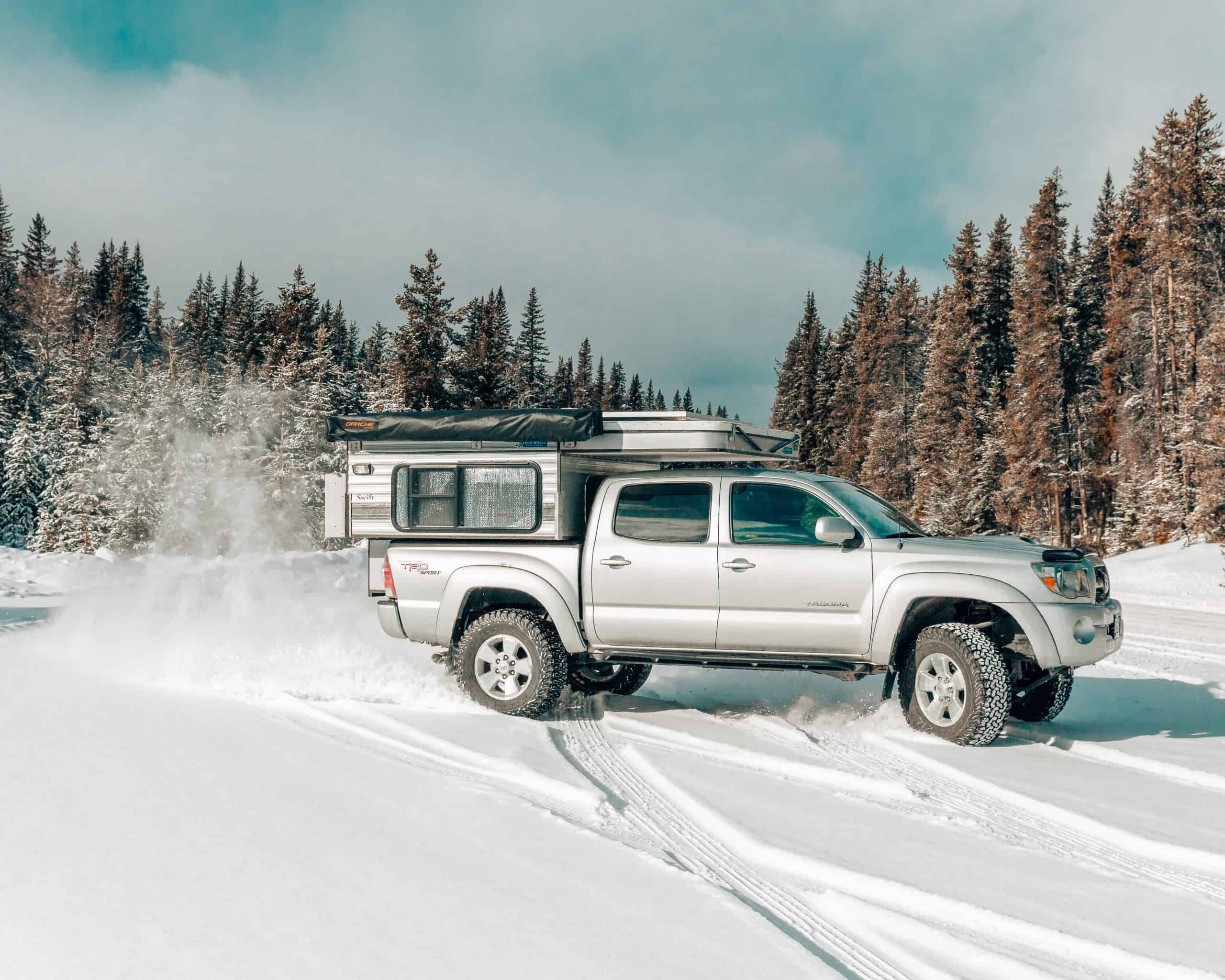 Toyota Tacoma and Four Wheel Camper Swift Model Drifting in the Snow
