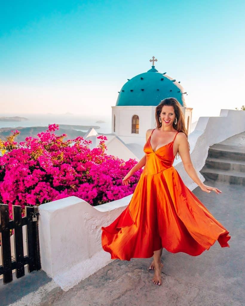 Bettina twirling in orange dress at blue dome church in Imerovigli Santorini