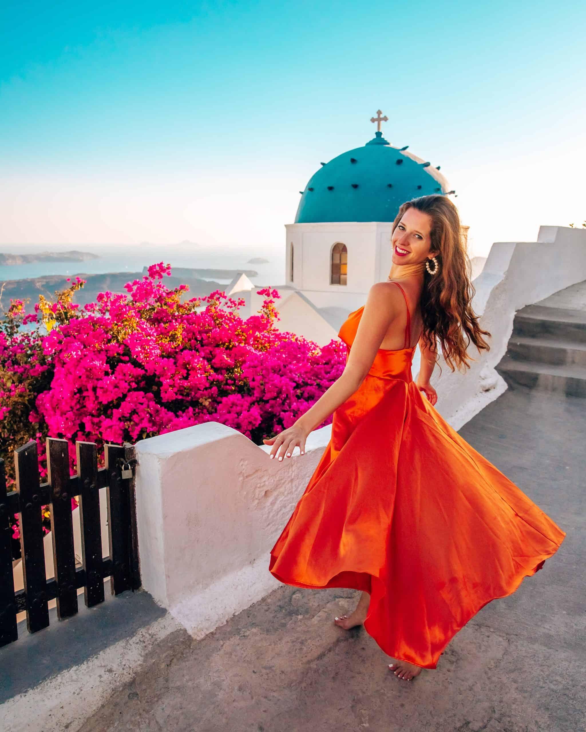 Bettina twirling at Blue Dome Church in Imerovigli, Santorini
