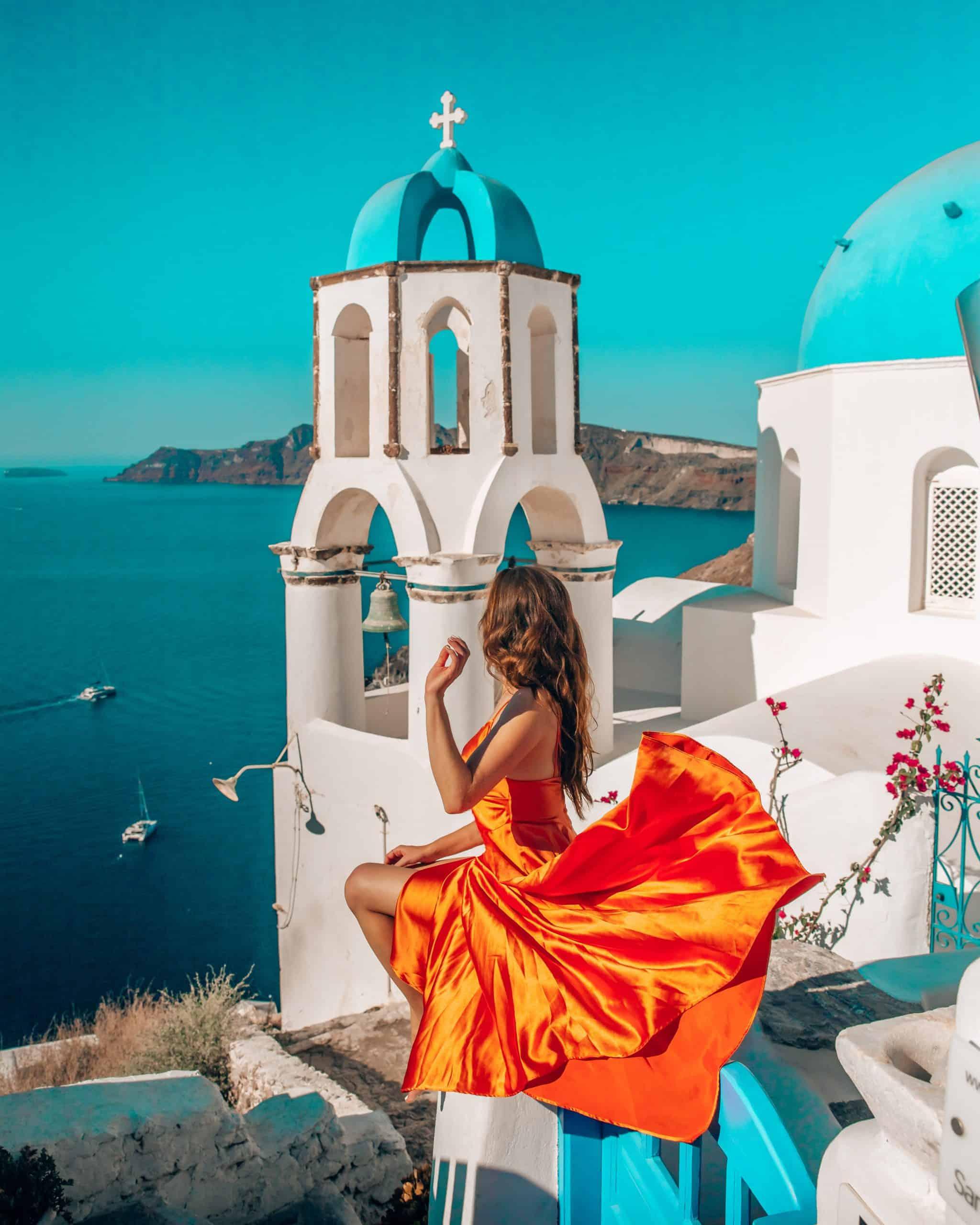 Bettina in Orange Dress at Blue Dome Church in Oia, Santorini