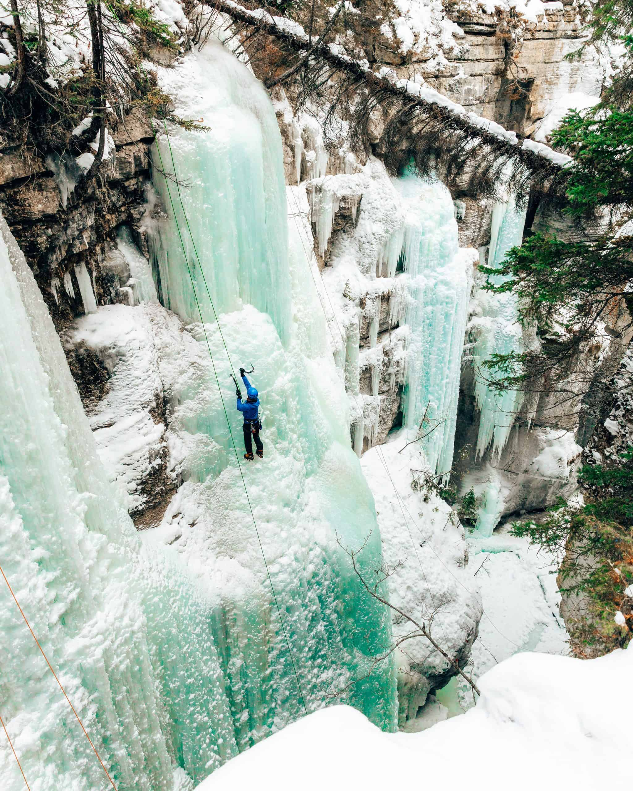 Ice Climber climbing up Frozen Waterfall at Maligne Canyon Jasper in Winter