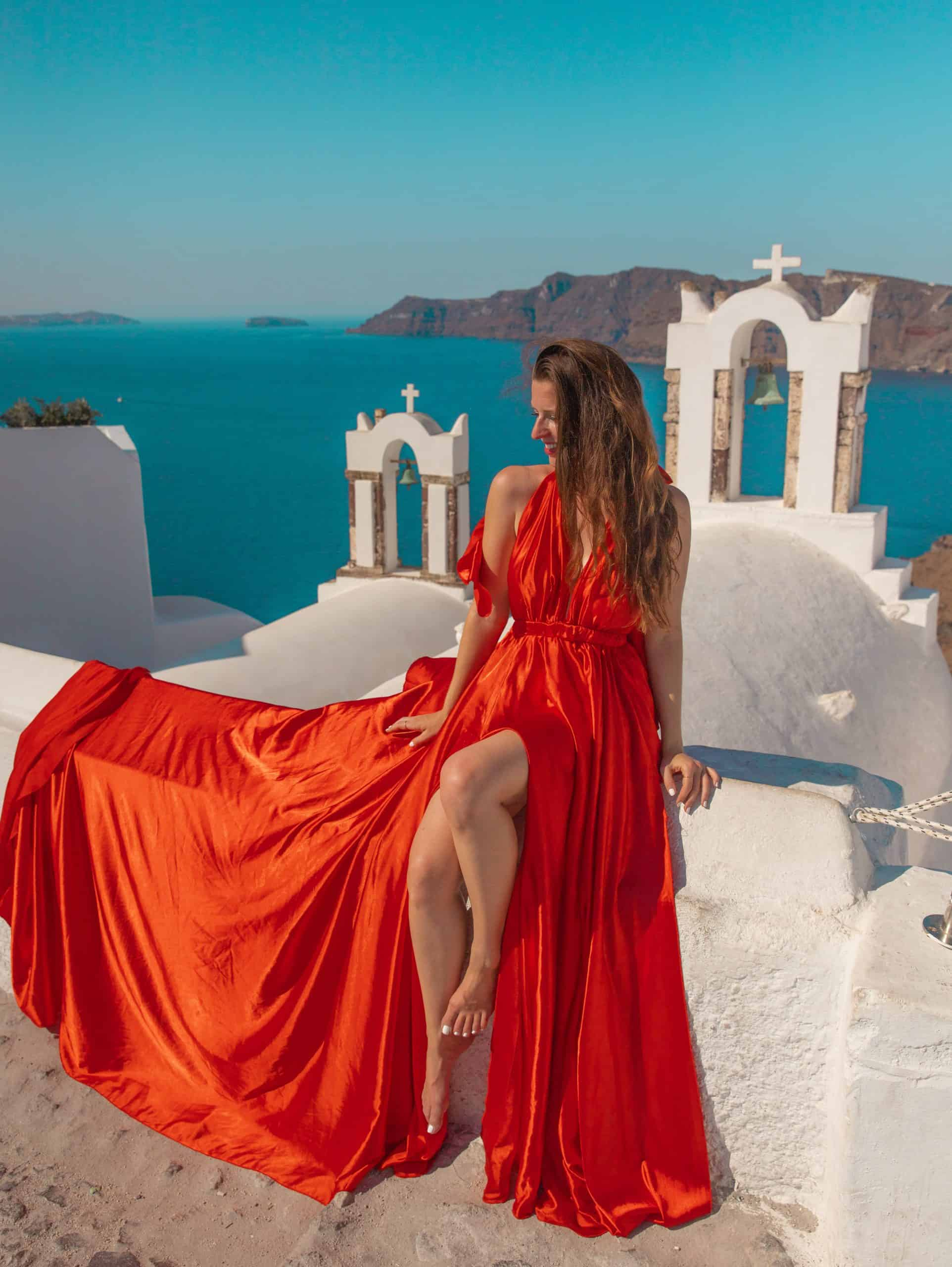 Bettina in Red Dress at Greek Church Bells with Ocean Views in Oia Santorini