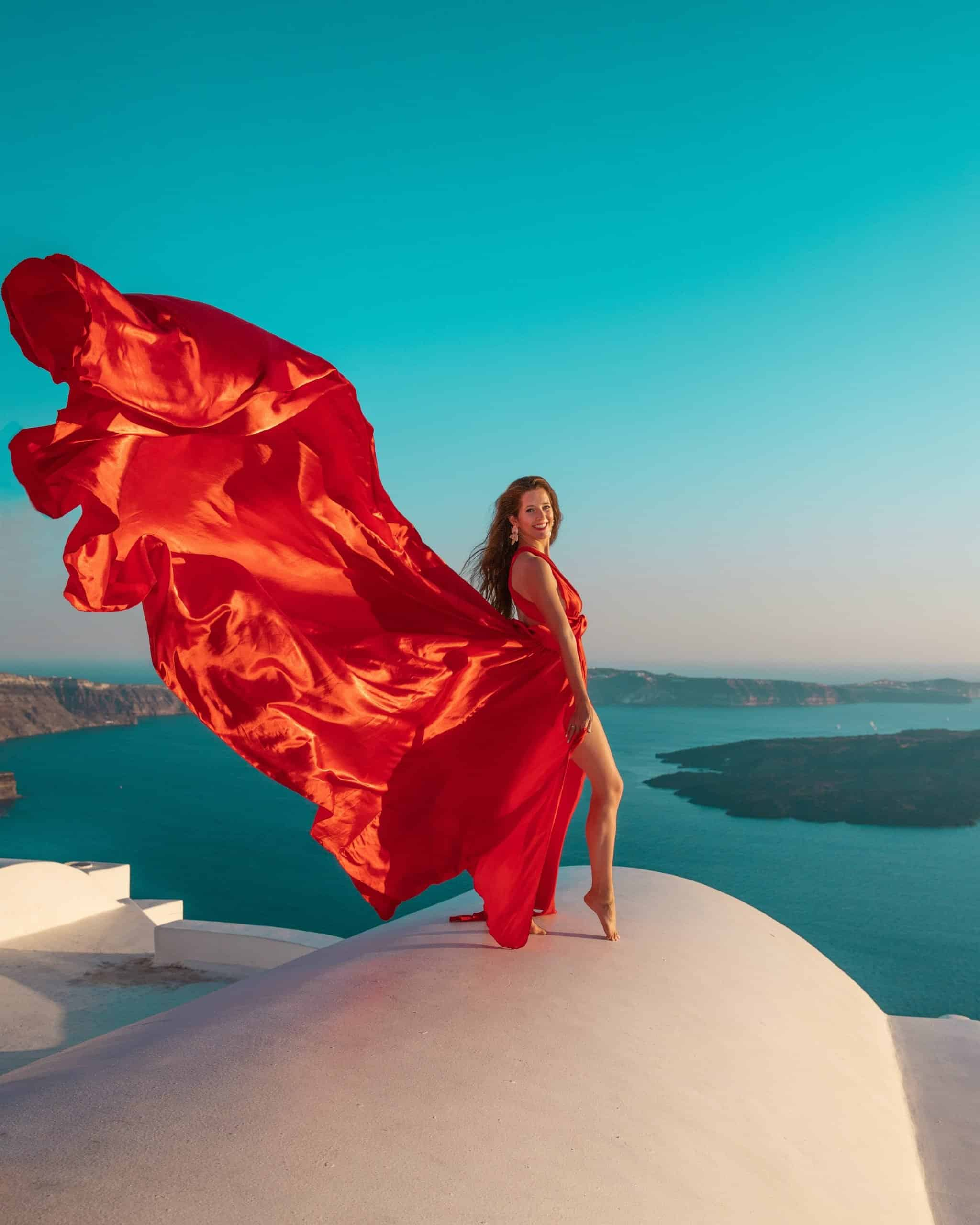 Bettina in Flying Red Dress on Santorini Rooftop in Imerovigli