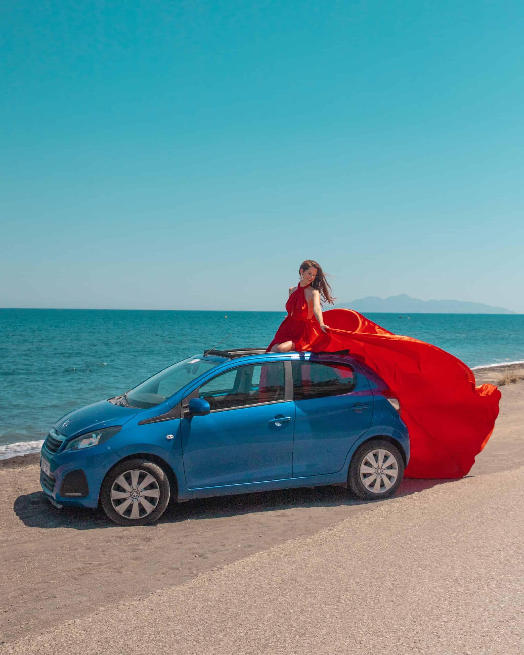 Bettina in red dress in blue rental car