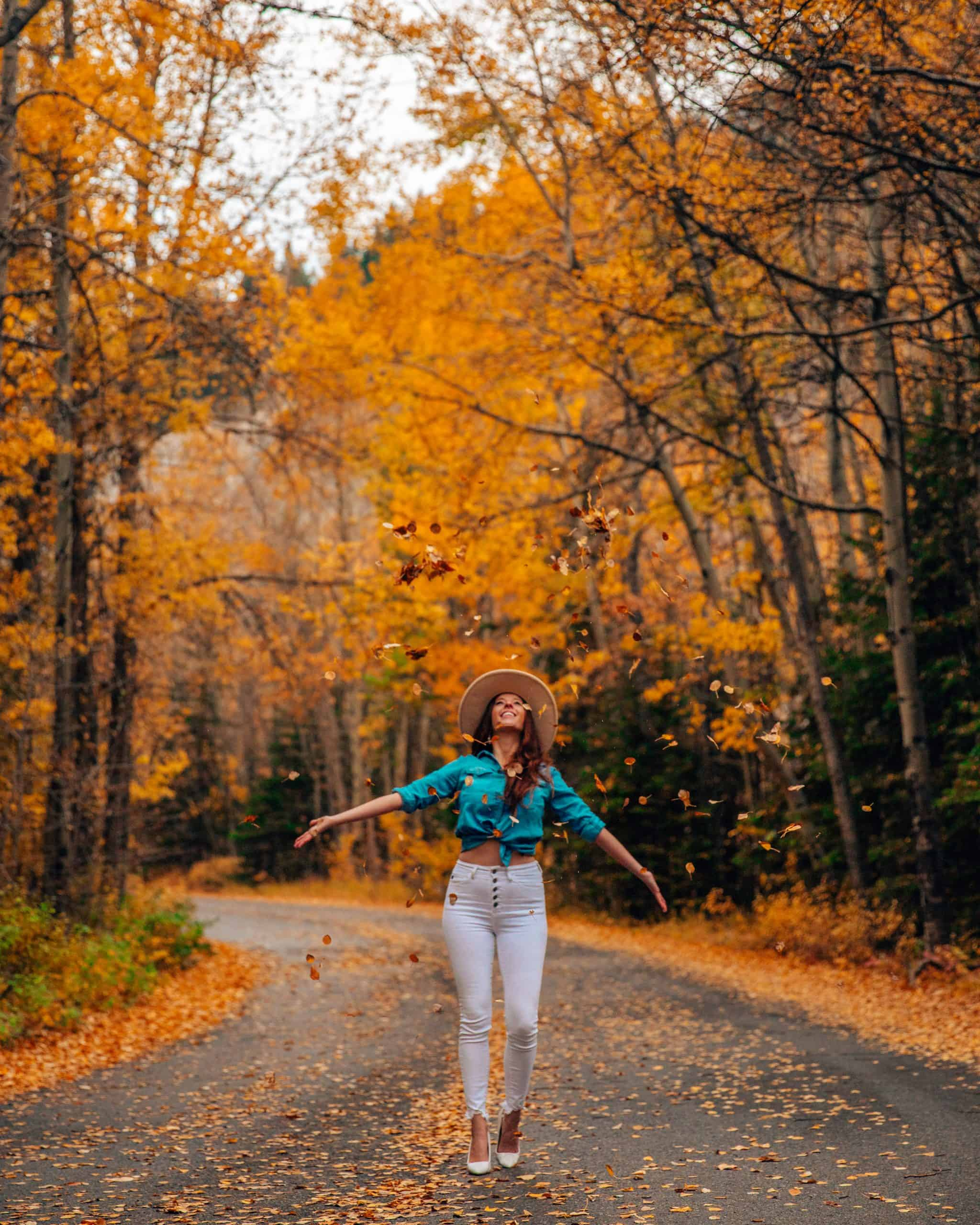 Bettina Throwing Leaves in Banff National Park in Fall